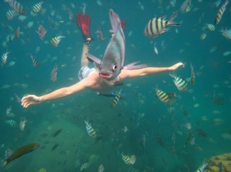 A man in the water with a fish in front of his face