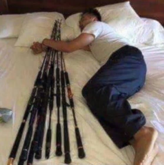 A man in bed with fishing poles
