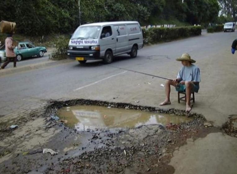A boy fishing in a hole in the street