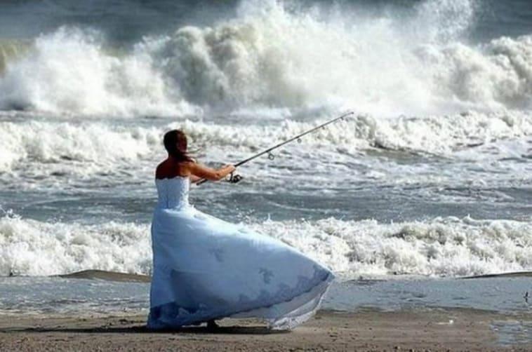 A woman fishing in a wedding dress