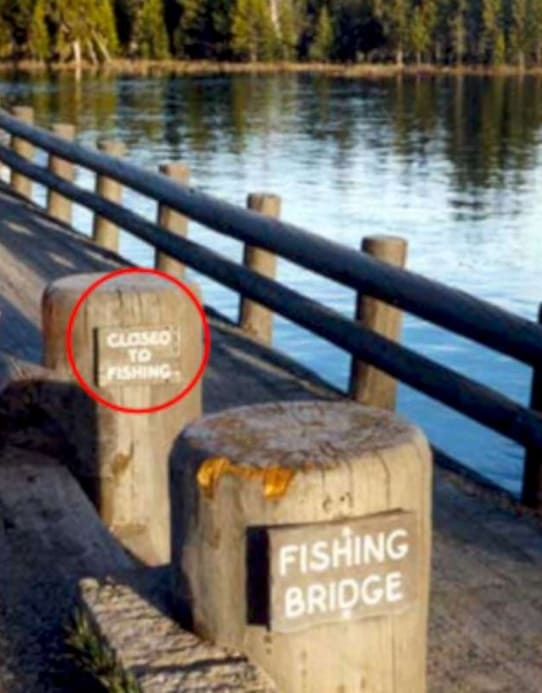 A fishing bridge with two signs