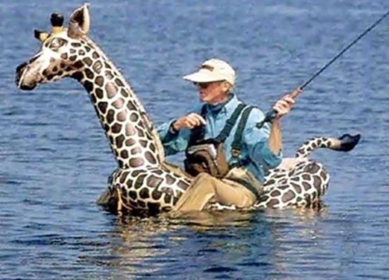 A man fishing while sitting on a blow-up giraffe