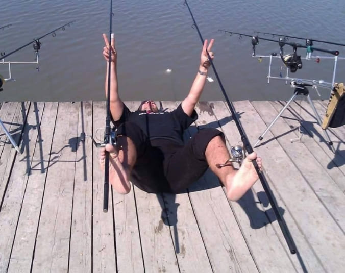 A man holding two fishing poles by his feet
