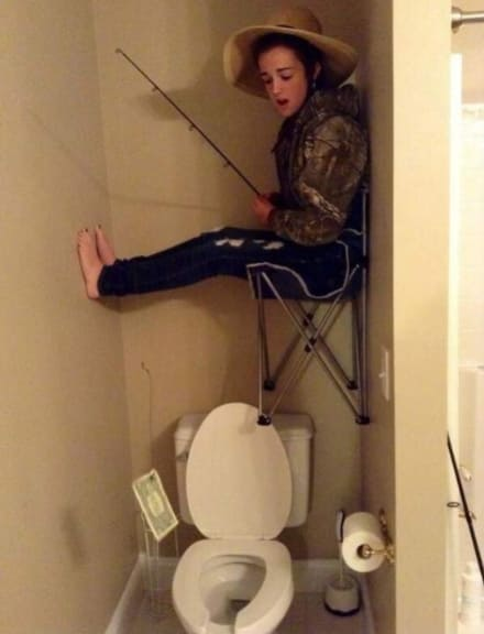 A boy ready to fish on the toilet