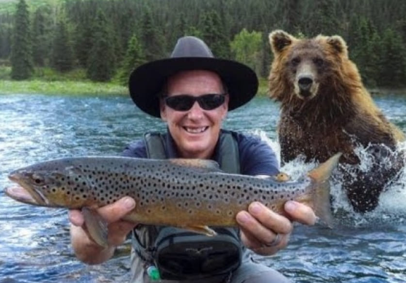 A man holding a fish in front of a bear
