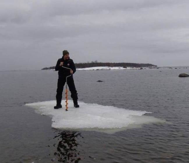 a man on ice in the middle of the water