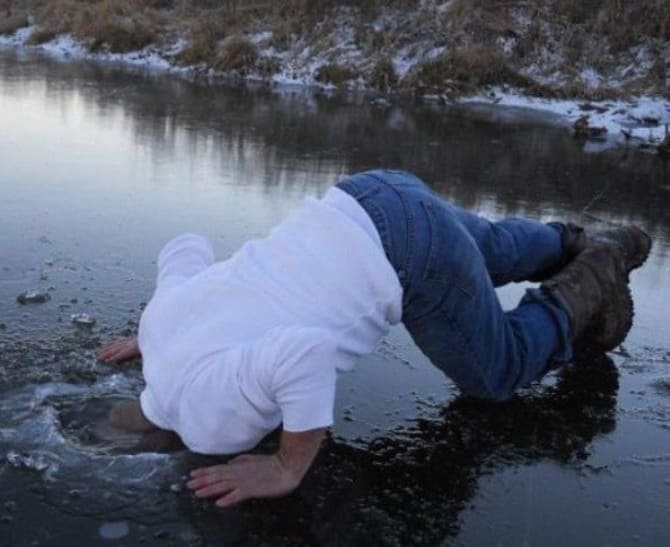 A man dunking his head in the river