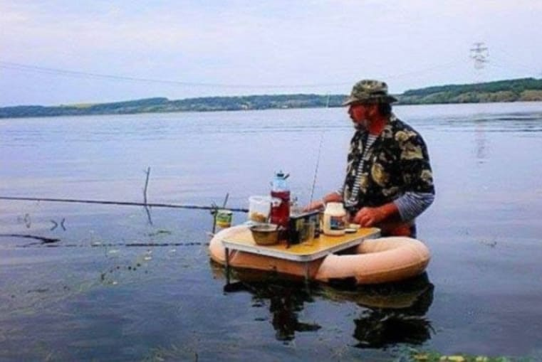 Man eating and fishing on the water
