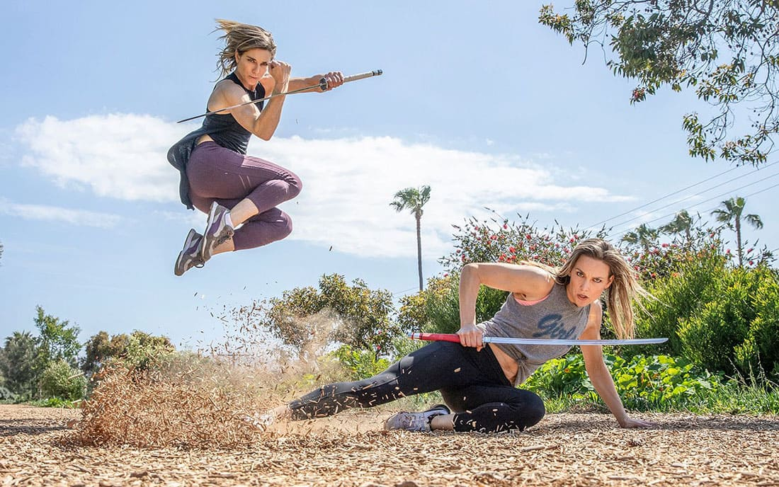 Two woman working out with swords
