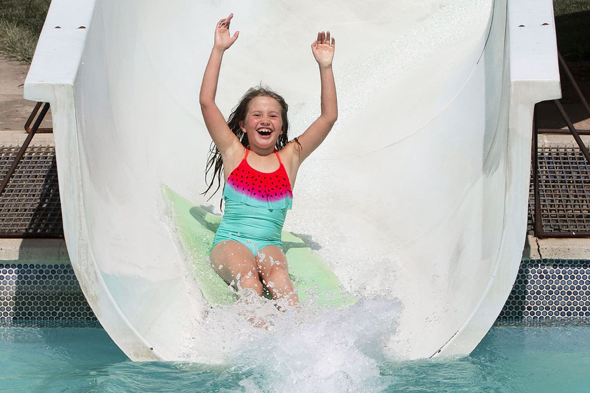 A little girl sliding down a water slide