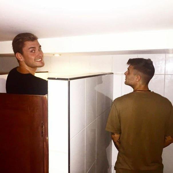 Two tall men taller than bathroom stalls