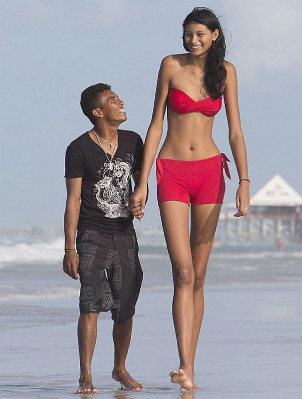 An extremely short man and tall woman walking hand in hand