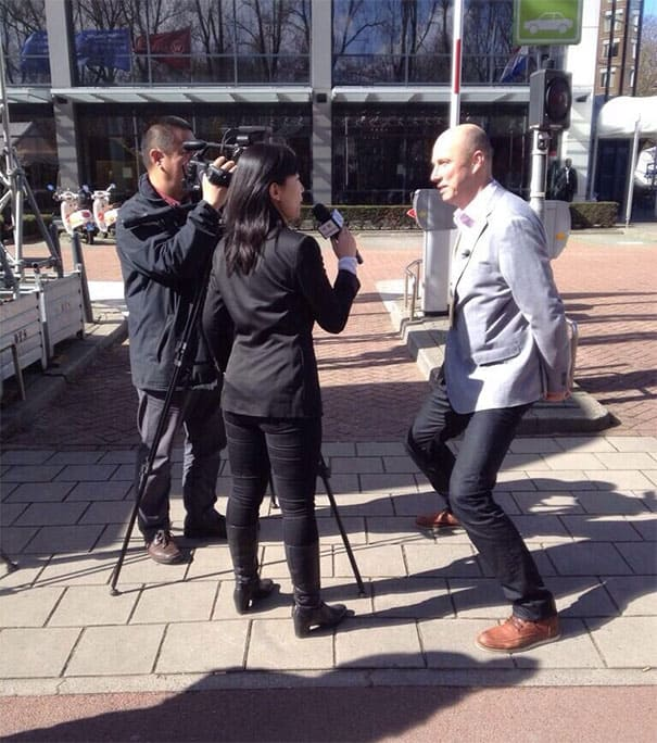 Small reporters interviewing a tall dutchman