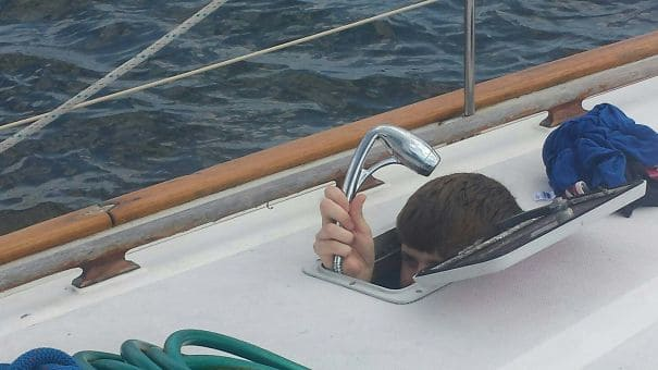Man taking a shower on a boat with his head coming out the roof of the boat