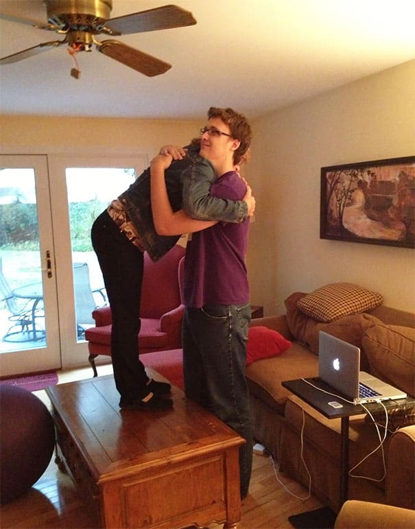 Short mom standing on the table to hug her large son