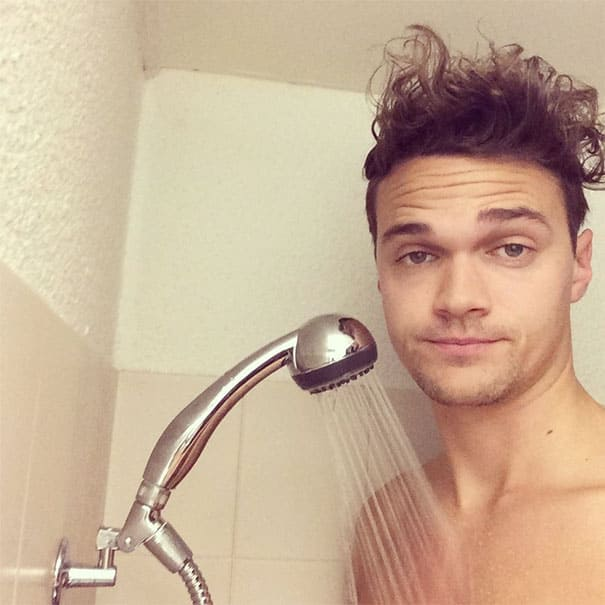 A man is too tall for the shower, the head reaches his throat