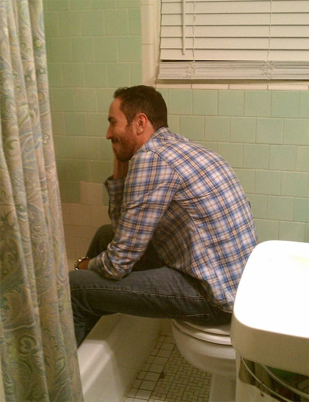 Tall man sitting on the toilet with his long legs in the bath