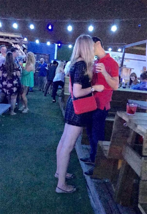 A couple kissing, however, the woman as tall and he's a miniature.