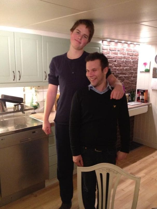 A tall man and his short friend posing for a picture