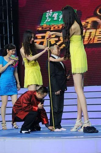 Tall women measuring a tiny man