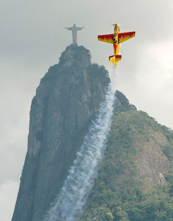 Plane flying up next to the Jesus statue in Brazil