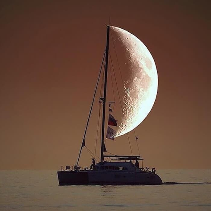 Sailboat in front of the moon
