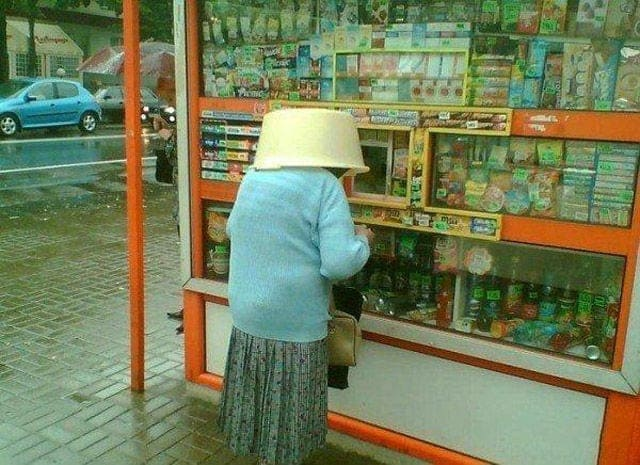An older Russian woman with a basket upside down on her head to keep dry from the rain.