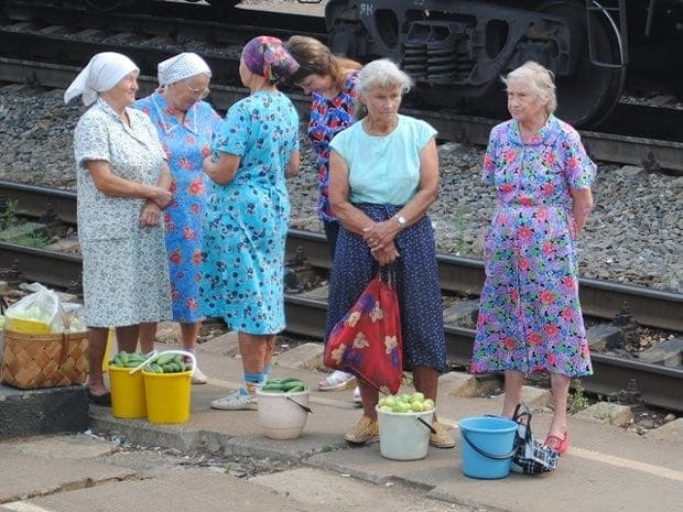 Babushka vendors line up to sell vegetables.