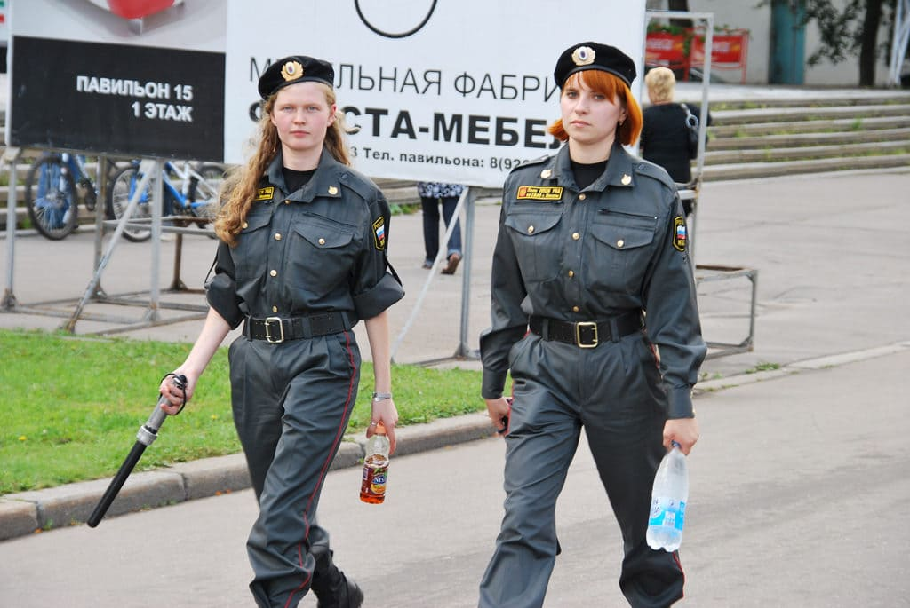 Two female Russian police officers holding a baton and soft drinks while protecting and serving.