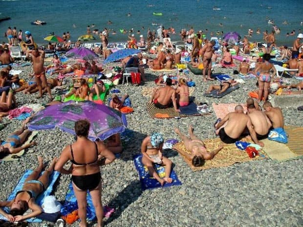 People on the Sochi beach tanning and playing on the ground covered in stones.
