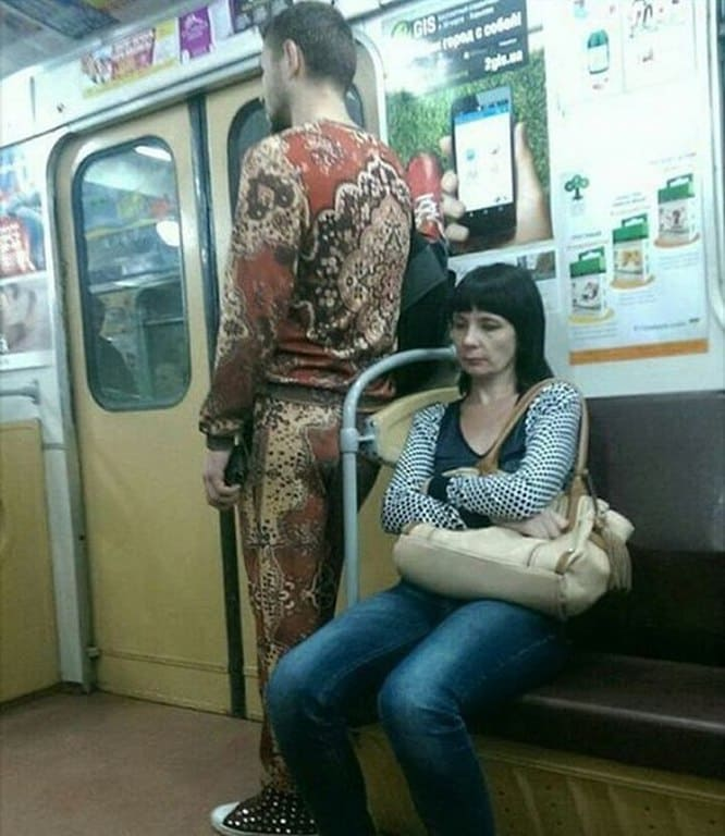A Russian man standing on the train wearing a sweatsuit that seems to be made out of an antique red carpet.