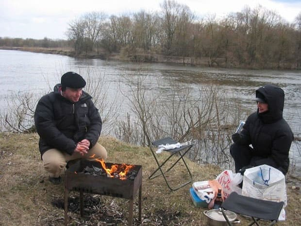 A man and woman are sitting next to a lake grilling in what looks like freezing temperatures.