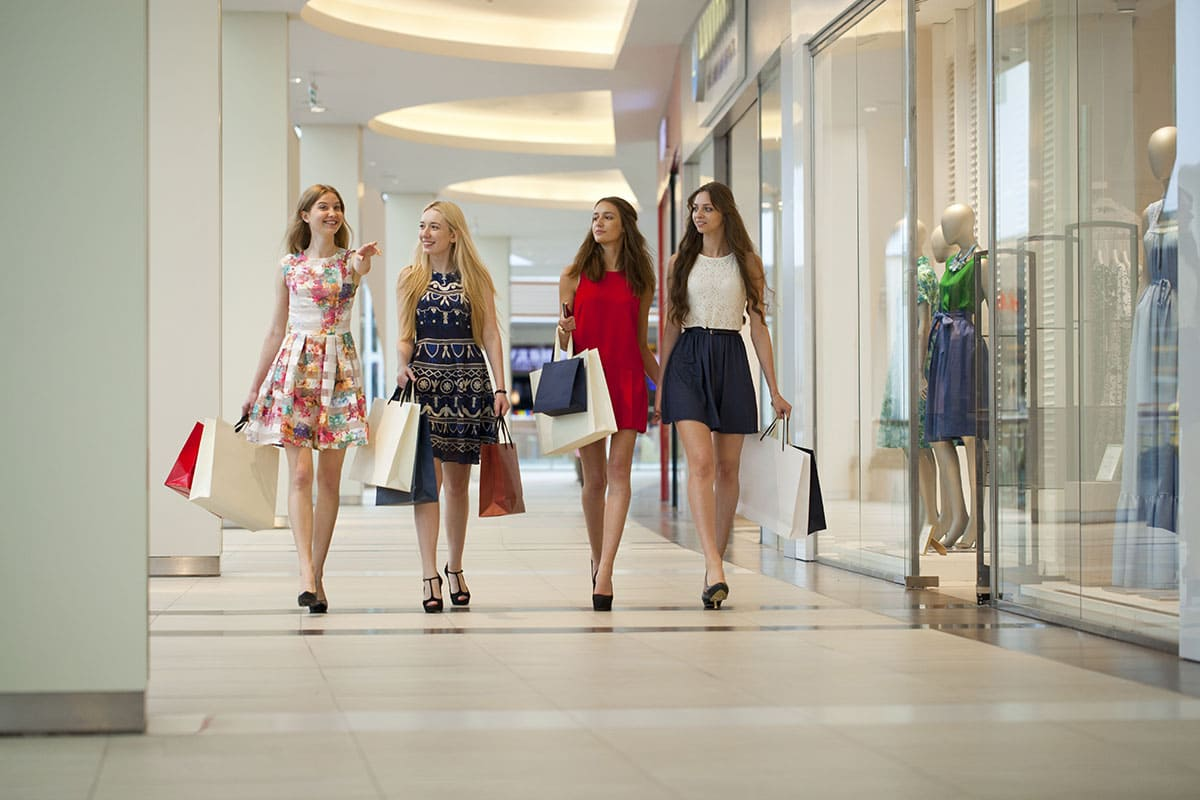 Four Russian women are walking through the mall with their hands full of bags of new clothes and accessories.