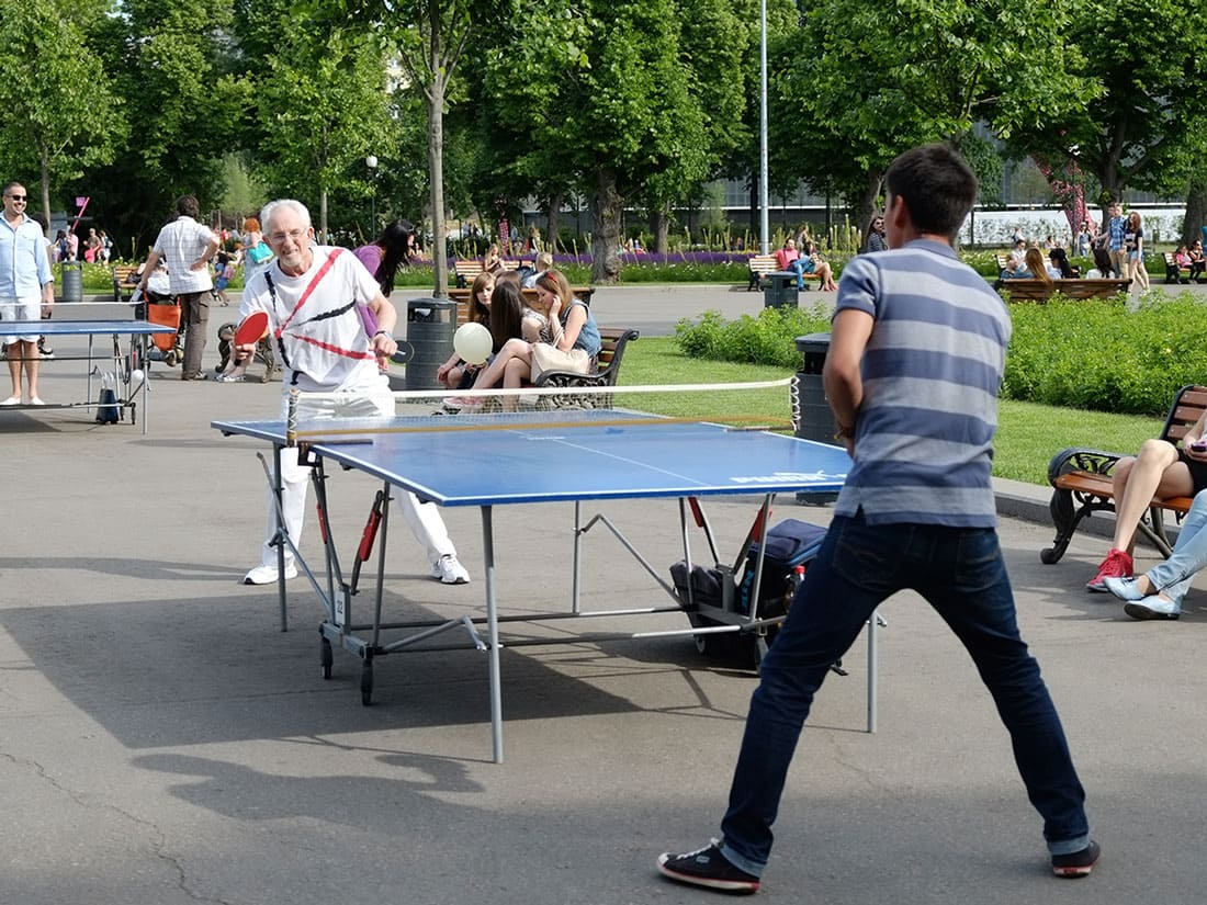 An old and young man playing table tennis in the park on July 20th, 2016, in Gorky Park, Moscow.