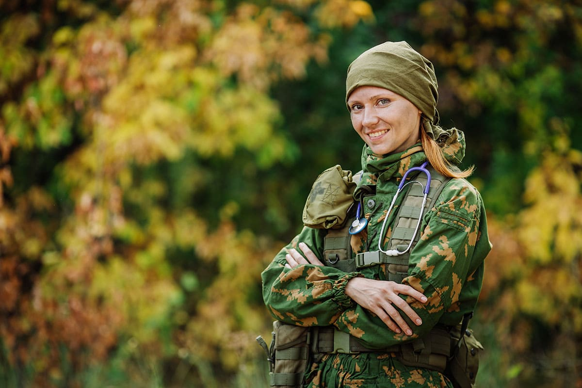 Female Russian soldier medic in universal camouflage army uniform and stethoscope.