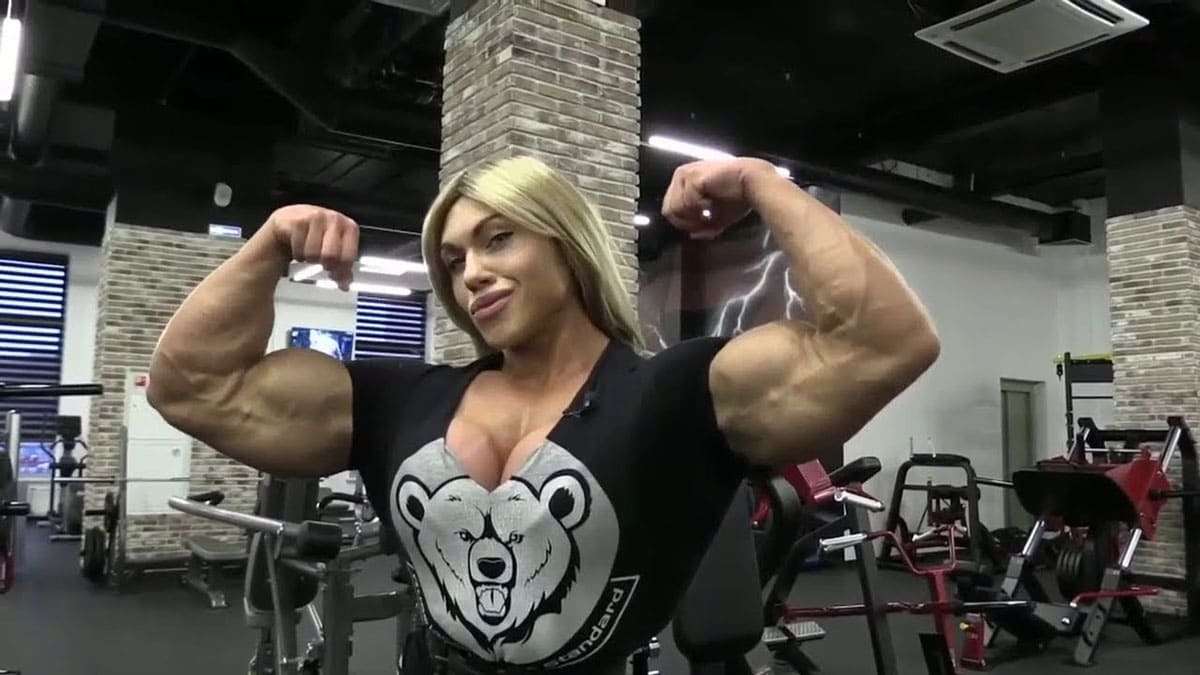 A strong Russian woman at the gym flexing her large biceps.
