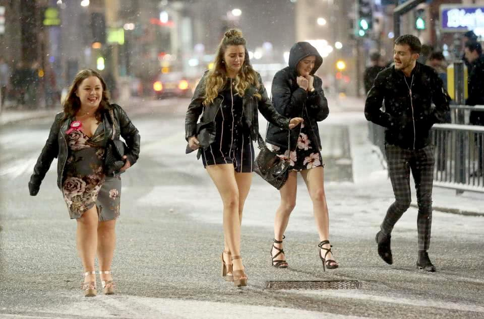 A group of approximately 20-year-old girls wearing shorts, short dresses and tall heels on St. Patrick's day with a man who looks the same age dressed warmly.