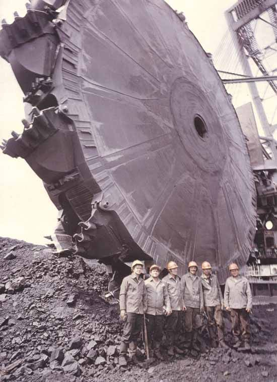 A photo of minors back in the day on their lunch break standing next to a large mining wheel.