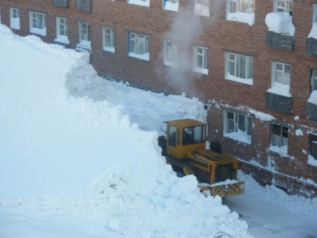 A tractor plowing two stories of snow in a severe Russian snowstorm.