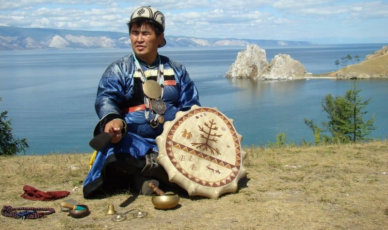 A native Siberian shaman sitting with beads and other holistic items with the beautiful ocean and mountains in the background.