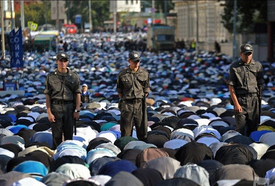 Photographed above are hundreds of Muslims taking part in daily prayer in the streets of Russia while multiple soldiers are standing amongst them.