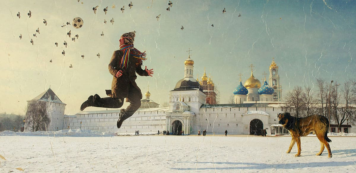 A man playing soccer next to his dog in one of Russia's many squares.