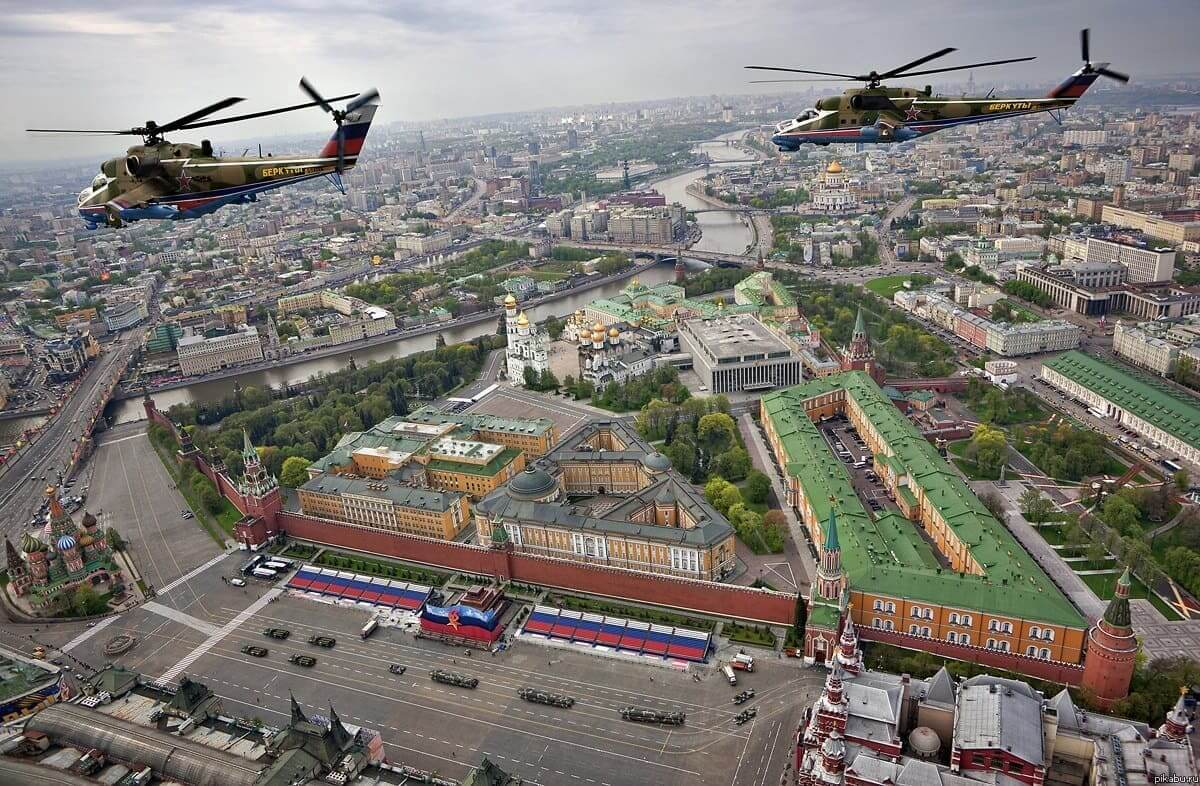 Russian military helicopters flying over the local military parade with a beautiful view of the Red Wall in Moscow.