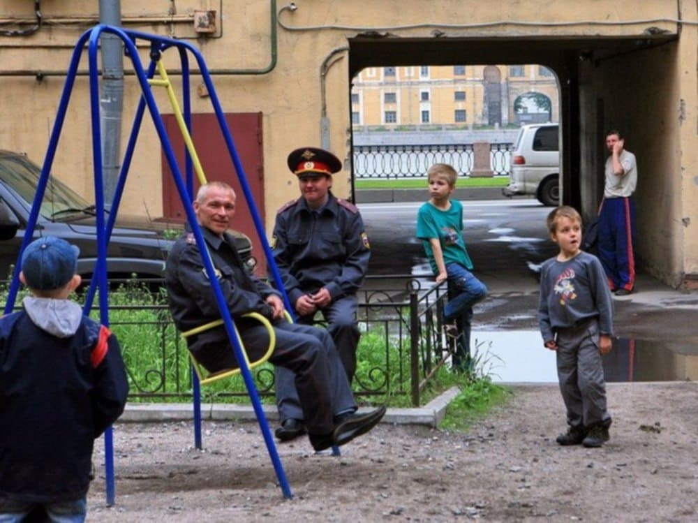 Russian police officers hang out at the playground with a few young boys with a random man sitting on the side.