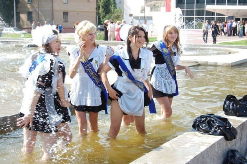 Female Russian students splashing around and taking photos in the fountain outside of the university.