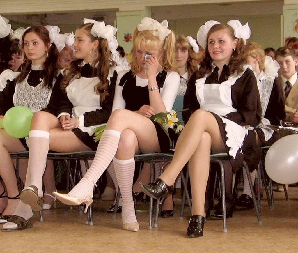 Russian school girls sitting cross-legged and wearing a white or black apron over their uniforms.