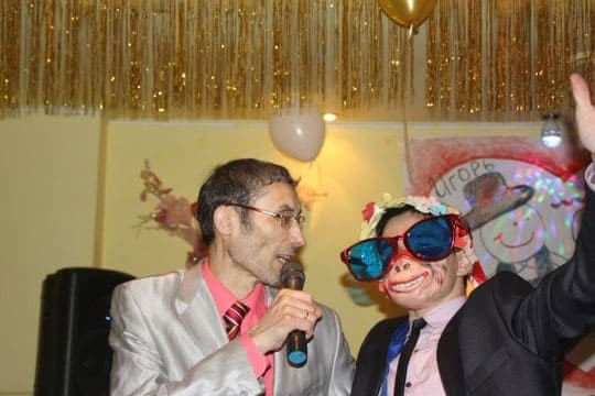 A wedding attendee with the local MC doing karaoke at a wedding in Russia.