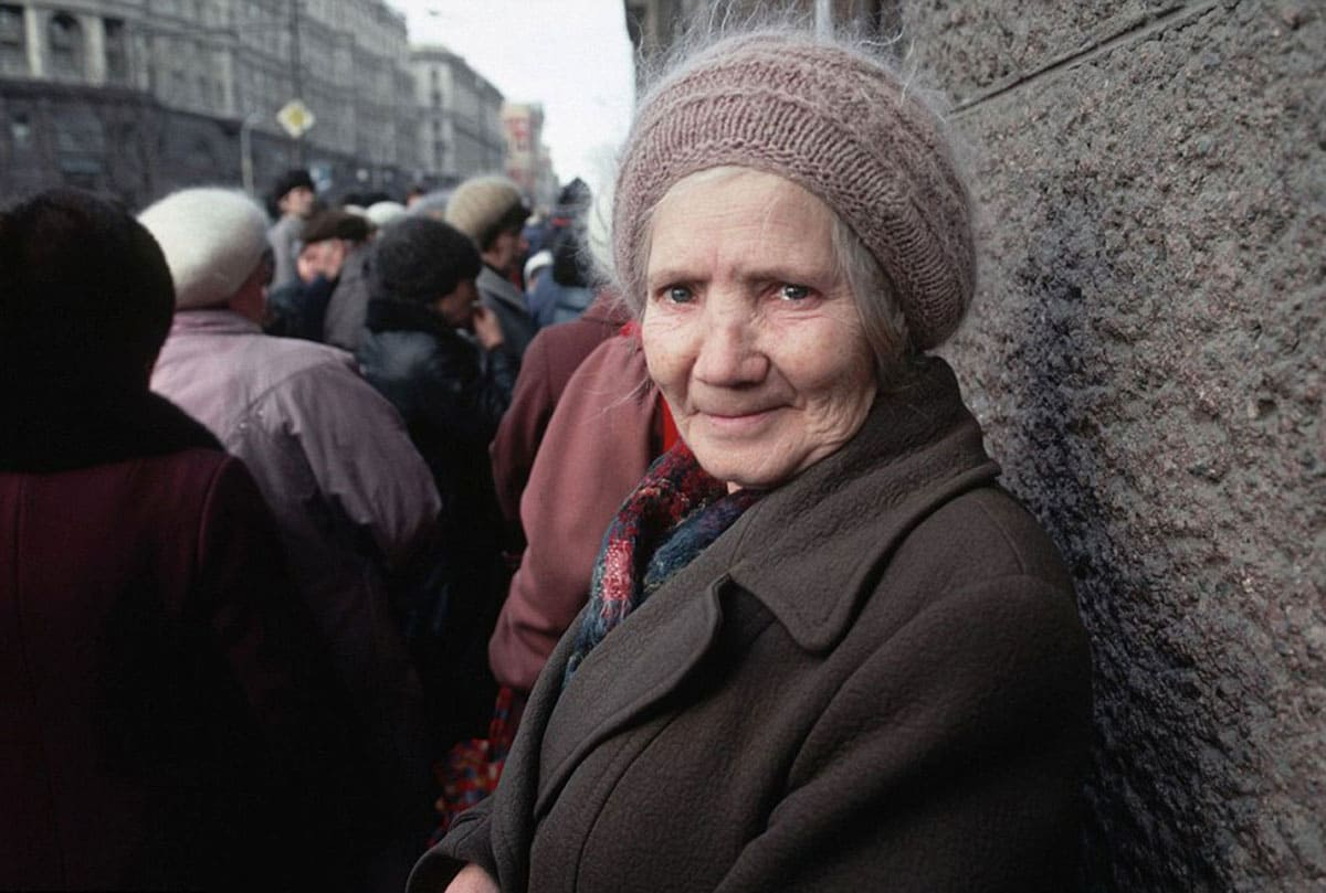An elderly woman stands with a brave face near the back of a queue for a market in the Russian capital.