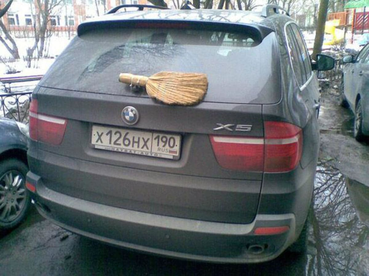 Above is a photo of a broom head attached to the back of a car's windshield to fix the broken windshield wipers.