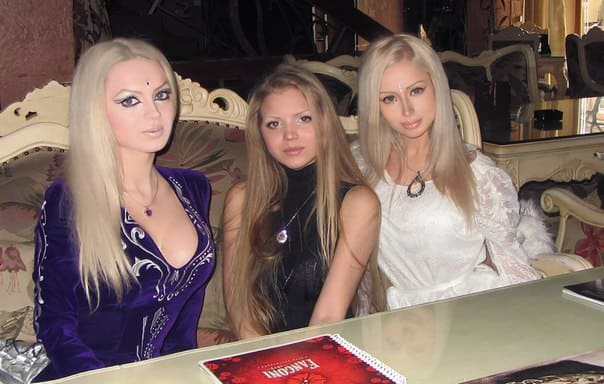 Three young Russian women with blonde hair, contoured makeup, and specially made outfits.